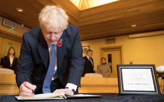 Thủ tướng Anh Boris Johnson viết vào sổ chia buồn với 39 nạn nhân chết trong thùng xe tải ở hạt Essex ngày 28-10. Ảnh: PA