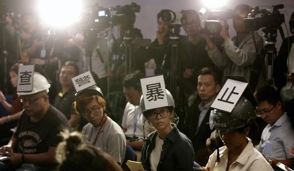 """Các nhà báo đội nón bảo hiểm có dòng chữ mang nội dung """"Điều tra sự bạo lực của cảnh sát"""", phản đối bạo lực của cảnh sát với cánh nhà báo, trong khi tham gia một cuộc họp báo của cảnh sát ở Hong Kong ngày 4-11. Ảnh: AP"""