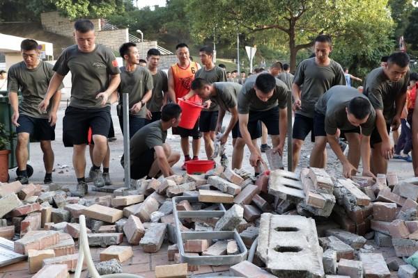 Binh sĩ quân đội Trung Quốc dọn dẹp gạch đá trên đường bên ngoài trường đại học Baptist. Ảnh: SCMP
