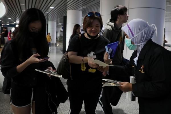 Nhân viên y tế Malaysia phân phát tờ rơi về virus corona cho hành khách tại sân bay quốc tề Kuala Lumpur (Malaysia) ngày 21-1. Ảnh: REUTERS
