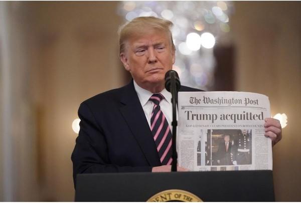 Tổng thống Mỹ Donald Trump cầm một tờ báo Washington Post đưa tin ông được Thượng viện tuyên trắng án, khi phát biểu tại Nhà Trắng ngày 6-2. Ảnh: REUTERS