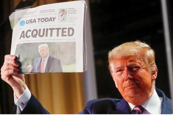 Tổng thống Mỹ Donald Trump cầm một tờ báo USA Today đưa tin ông được Thượng viện tuyên trắng án, khi phát biểu tại buổi lễ ăn sáng cầu nguyện quốc gia thường niên ở thủ đô Washington (Mỹ) ngày 6-2. Ảnh: REUTERS