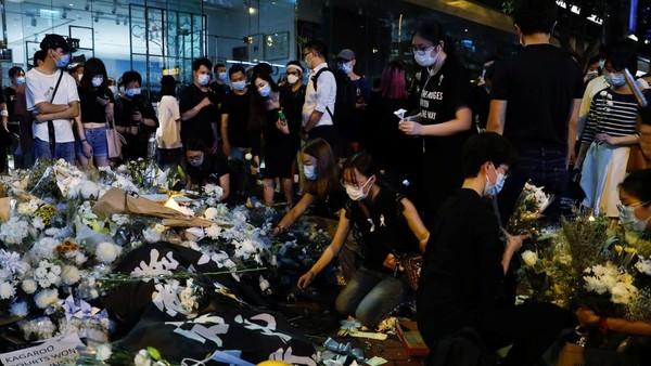 Hoa được đặt tại nơi người biểu tình Marco Leung Ling-kit rơi từ một giàn giáo xuống và chết trong cuộc biểu tình tại Hong Kong một năm trước, ngày 15-6. Ảnh: Tyrone Siu/REUTERS