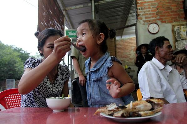 Bé Lan Anh về thăm nhà cũ được mẹ Nguyễn Thị Thu Trang chăm từng muỗng cơm. Ảnh: HOÀNG GIANG