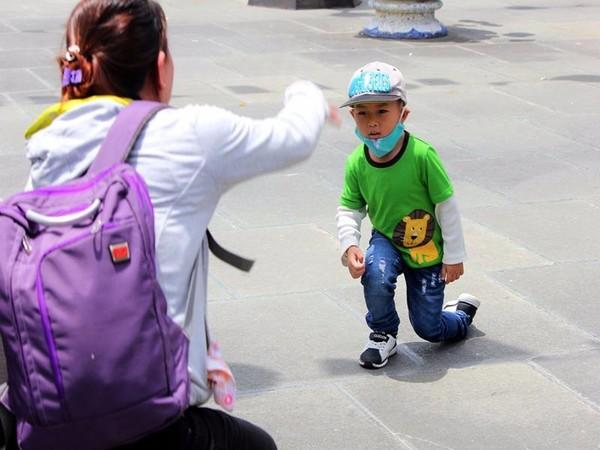 Một em nhỏ được mẹ chụp hình khi đến chùa.