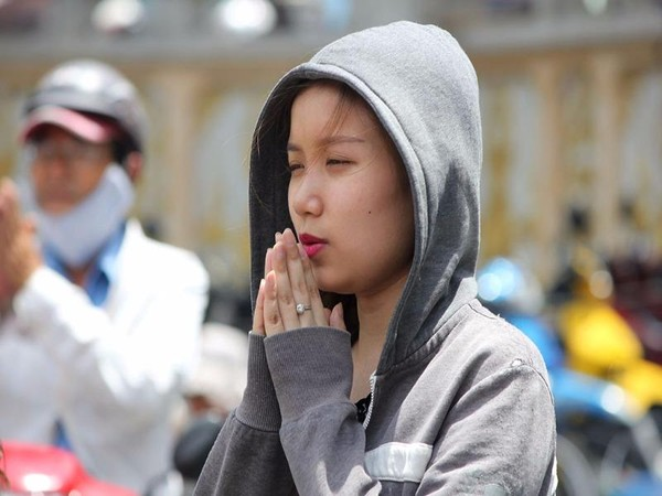 Cô gái đội nắng cầu nguyện trước tượng Quan Âm