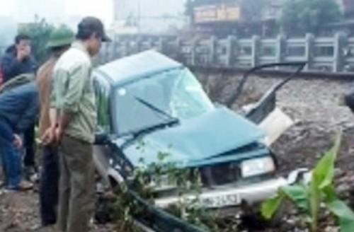Ô tô bị biến dạng, nằm cạnh đường ray, tài xế và một người trong xe bị thương nặng. Ảnh: Sơn Dương