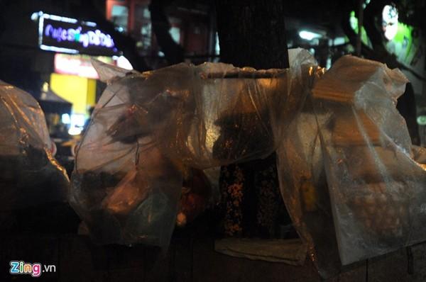 Trời mưa khiến việc buôn bán cũng trở nên khó khăn, ế ẩm hơn ngày thường. Trong ảnh: Người phụ nữ bán hang rong trên đường Nguyễn Văn Cừ (quận 5) đang ngồi trong mưa chờ khách mua hang.