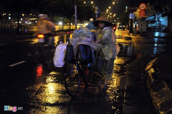 Một người phụ nữ dắt xe dưới trời mưa trên đường Võ Văn Kiệt (quận 6).