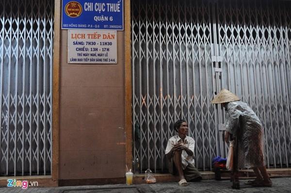 Những người cùng cảnh ngộ. Hai ông bà bán vé số dạo đang trú mưa tại đường Hồng Bàng (quận 6).