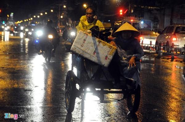 Hai vợ chồng xe ba gác đi dưới mưa trên đường 3 tháng 2 (quận 10).
