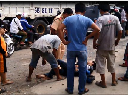 Một nạn nhân bị thương bất tỉnh nằm giữa đường và được đưa đi cấp cứu sau đó