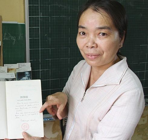 Cô Lao Thị Tư (giáo viên Trường tiểu học Trưng Vương, Sa Đéc) giới thiệu những quyển sách của M.Duras do người thân của nữ văn sĩ tặng - Ảnh: V.Tr.