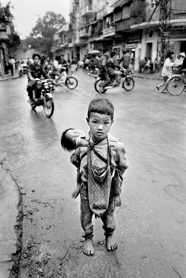"""Cậu bé """"địu"""" em trên lưng - Ảnh chụp năm 1992 tại Hà Nội"""