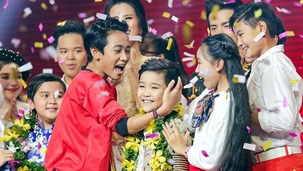 Trịnh Nhật Minh trong vòng tay của các thí sinh nhí thời khắc đăng quang ngôi vị quán quân. Ảnh DÂN TRÍ