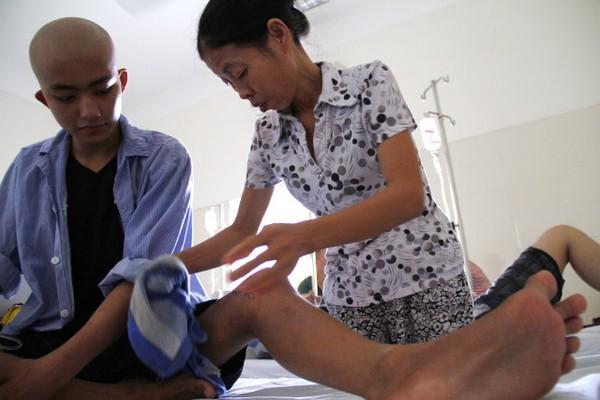 Sau mổ, vì chưa thể đi lại bình thường nên hầu như mọi sinh hoạt Thắng đều nhờ vào mẹ Hoa - Ảnh: Nam Trần