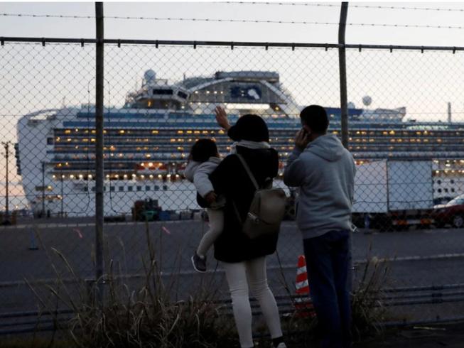 Người thân vẫy tay và nói chuyện qua điện thoại với khách trên tàu Diamond Princess đậu tại cảng Daikoku Pier Cruise ở Yokohama (Nhật). Ảnh: REUTERS
