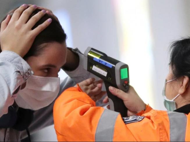 Một hành khách đến sân bay quốc tế Hong Kong đang được kiểm tra nhiệt độ. Ảnh: REUTERS