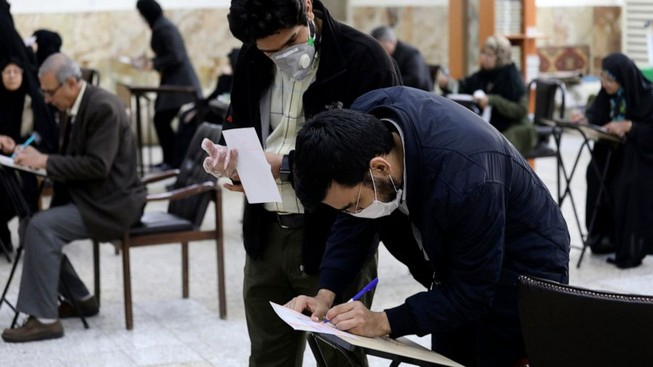 Cử tri ở Iran mang khẩu trang đi bỏ phiếu. Ảnh: AP