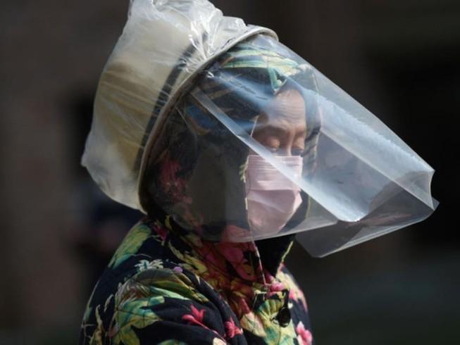 Một phụ nữ ở Vũ Hán dùng đồ bảo hộ khuôn mặt tạm thời để chống lây nhiễm COVID-19. Ảnh: REUTERS
