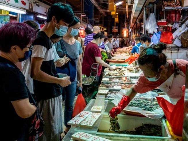 Nhiều người đeo khẩu trang khi đang đi chợ cá ở Hong Kong. Ảnh: AP/CNN