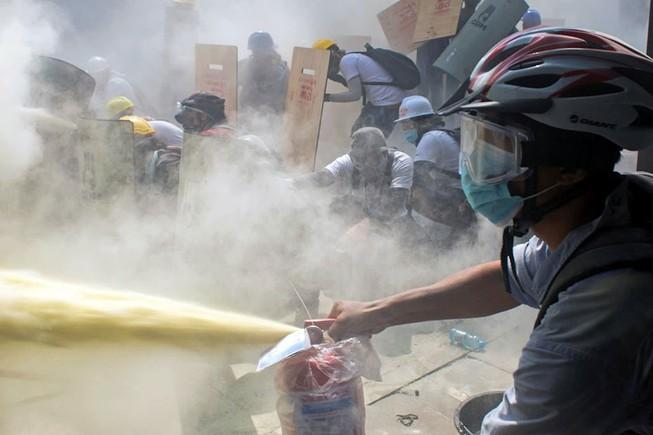 Người biểu tình Myanmar dùng khiên tự chế và bình cứu hỏa để cản lại hơi cay từ phía cảnh sát ở TP Yangon ngày 3-3.