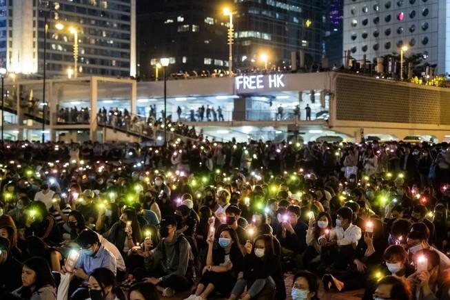 Người biểu tình chiếu đèn từ điện thoại di động của họ trong một cuộc biểu tình tại Edinburgh Place ở quận trung tâm của Hồng Kông ngày 14-11. Ảnh: Bloomberg