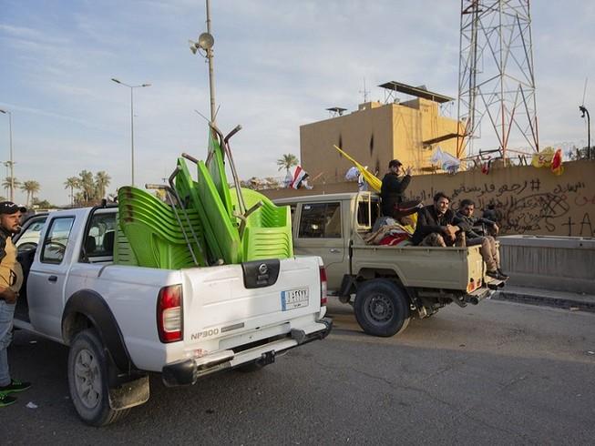 Người biểu tình thu dọn và rời khỏi Đại sứ quán Mỹ ở Baghdad. Ảnh: AP