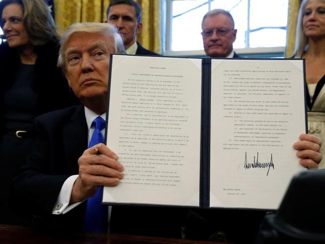 Tổng thống Donald Trump ký sắc lệnh cấm nhập cảnh năm 2017. Ảnh: AFP
