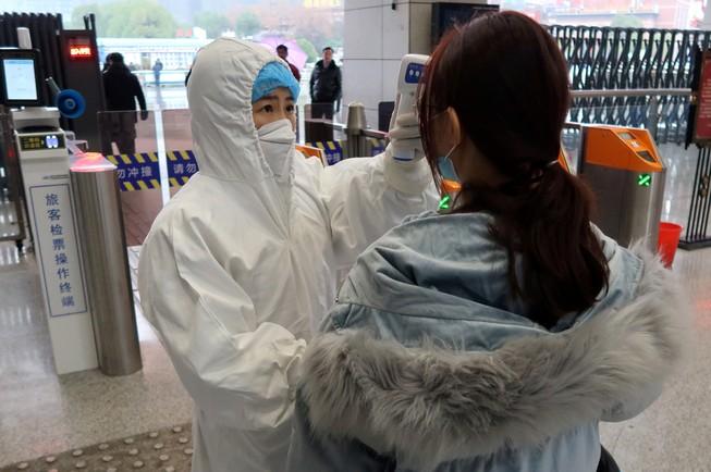 Nhân viên y tế ở tỉnh Hồ Bắc thực hiện kiểm tra giám định một hành khách đi tàu hôm 24-1. Ảnh: REUTERS