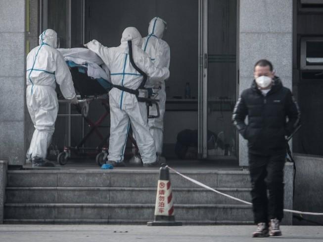 Nhân viên y tế tại một bệnh viện ở Vũ Hán đang di chuyển một nạn nhân nhiễm virus Corona hôm 31-1. Ảnh: AFP