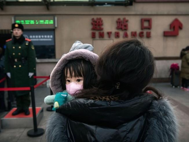 Một em bé cùng mẹ đứng đợi ở tàu ở ga Bắc Kinh ngày 1-2. Ảnh: GETTY IMAGES