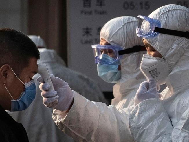 Nhân viên y tế Trung Quốc kiểm tra thân nhiệt của hành khách tại một ga tàu ở thủ đô Bắc Kinh (Ảnh chụp ngày 4-2). Ảnh: AFP