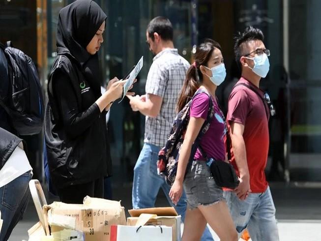 Một tình nguyên viên của Bộ Truyền thông Singapore thu thập phản hồi của người dân về tình hình dịch Corona. Ảnh: AFP