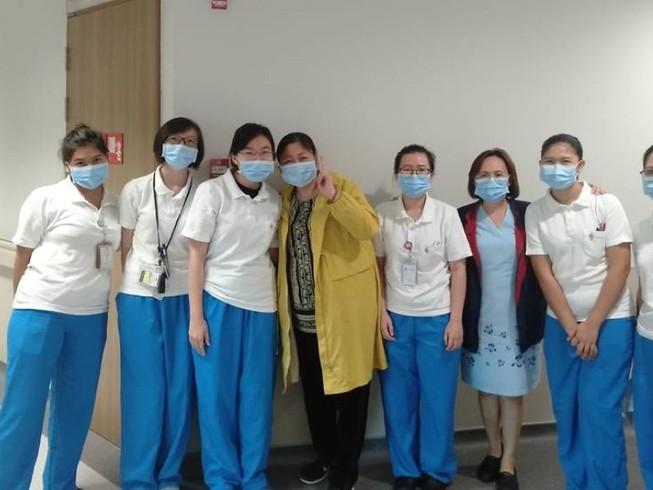 Bà Giang chụp ảnh cùng các y bác sĩ điều trị cho mình tại Trung tâm Phòng chống bệnh truyền nhiễm Singapore. Ảnh: CNA
