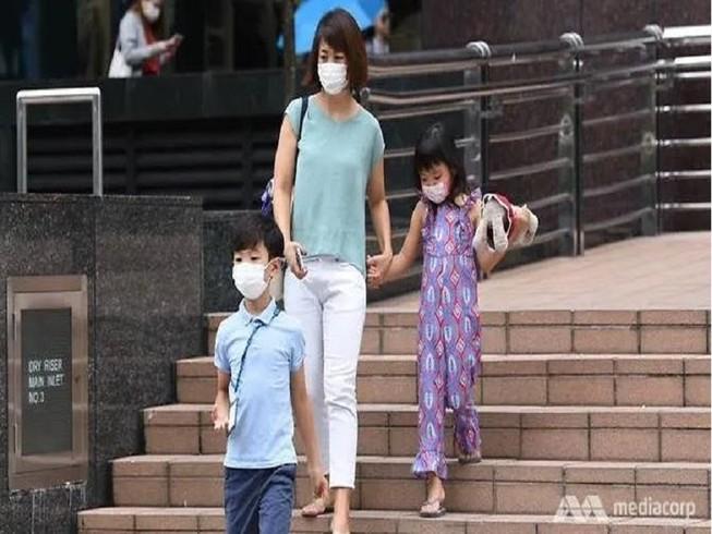 Người dân mang khẩu trang khi đi ra ngoài tại Singapore. Ảnh: CHANNEL NEWS ASIA