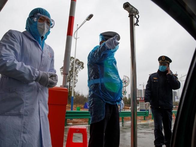 Một nhân viên y tế và hai cảnh sát tại một chốt kiểm dịch trên đường phố Vũ Hán (Ảnh chụp ngày 10-2). Ảnh: AP