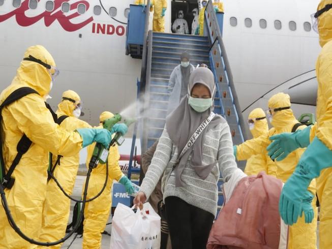 Nhân viên y tế phun thuốc khử trùng cho những người Indonesia được sơ tán khỏi Trung Quốc tại sân bay quốc tế Hang Nadim, quần đảo Riau ngày 16-2. Ảnh: BỘ NGOẠI GIAO INDONESIA