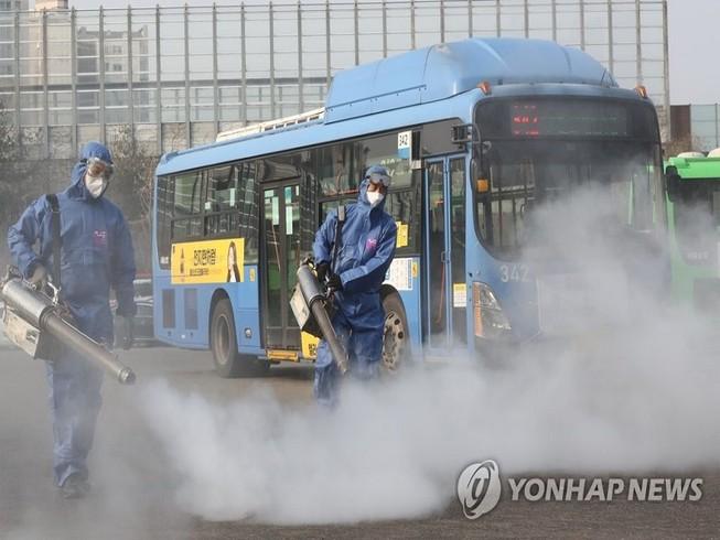 Các nhân viên y tế Hàn Quốc khử trùng tại một bến xe buýt ở thủ đô Seoul hôm 20-2. Ảnh: YONHAP