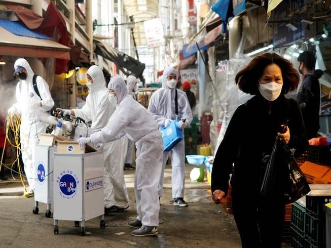 Một người phụ nữ đeo khẩu trang khi nhân viên của một y tế khử trùng một khu chợ truyền thống ở thành phố Seoul, Hàn Quốc. Ảnh: REUTERS