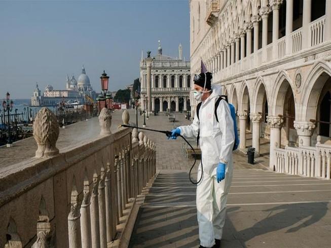 Nhân viên y tế khử trùng tại cầu Ponte della Paglia trên quảng trường Saint Mark ở TP Venice, Ý. Ảnh: REUTERS