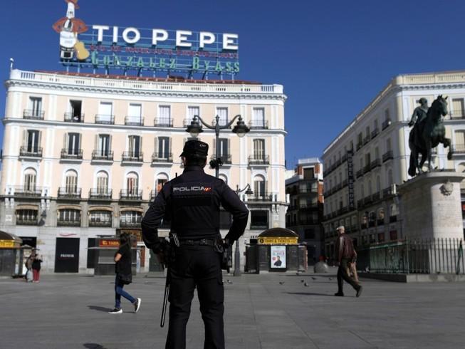 Một cảnh sát Tây Ban Nha đứng gác tại quảng trường Sol ở TP Madrid (Tây Ban Nha) ngày 10-3. Ảnh: AP