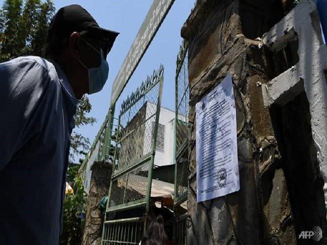 Người dân Campuchia đọc thông báo về đóng cửa trường học do đại dịch COVID-19. Ảnh: AFP