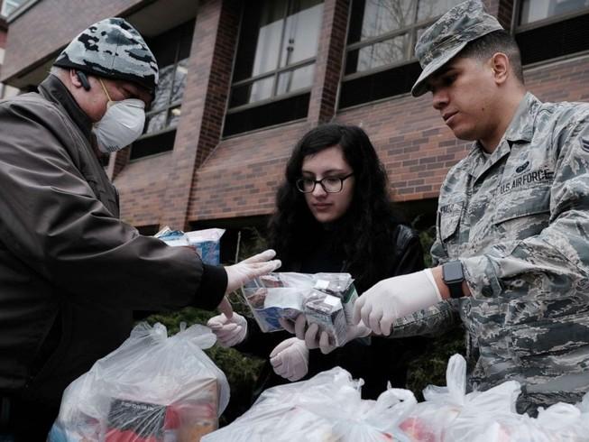 Một quân y Mỹ phát thực phẩm và trang thiết bị y tế cứu trợ cho người vô gia cư ở bang California ngày 14-3. Ảnh: AFP