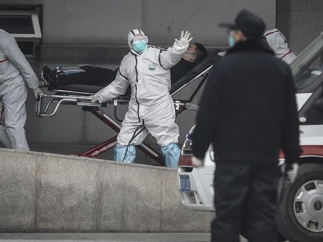 Nhân viên y tế di chuyển một bệnh nhân nhiễm COVID-19 ở Vũ Hán, Trung Quốc (Ảnh chụp ngày 17-1). Ảnh: AFP
