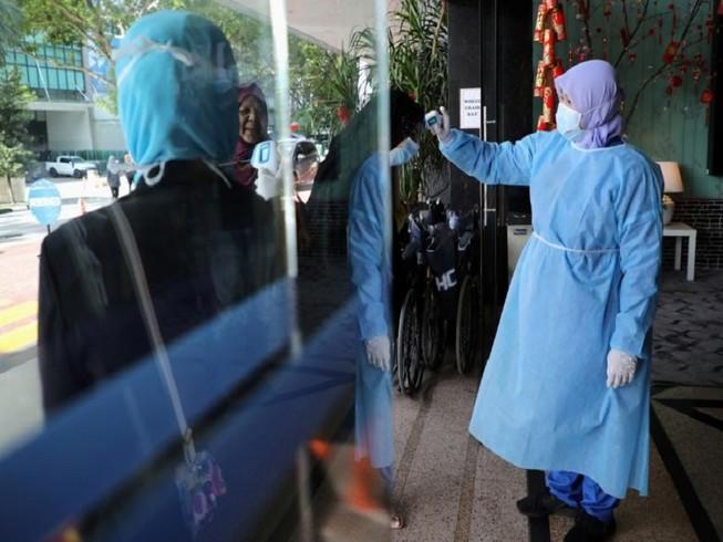 Nhân viên y tế kiểm tra thân nhiệt những người đi vào bệnh viện ở thủ đô Kuala Lumpur, Malaysia. Ảnh: REUTERS