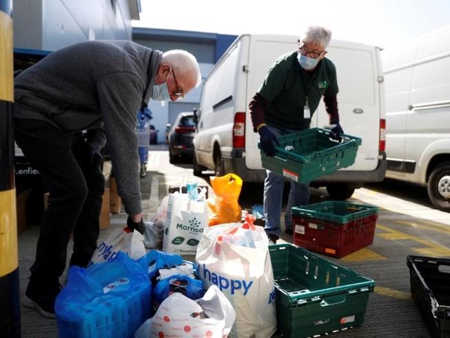Tình nguyện viên sắp xếp thực phẩm cứu trợ cho người thu nhập thấp ở quận Enfield, Anh ngày 25-3. Ảnh: REUTERS