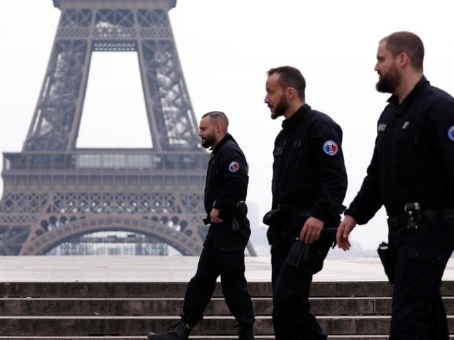 Cảnh sát Pháp tuần tra tại quảng trường Tocadero gần tháp Eiffel trong thời gian nước này phong toả (Ảnh chụp ngày 17-3). Ảnh: REUTERS