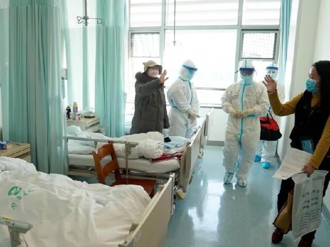 Một bệnh nhân được chữa khỏi COVID-19 ở Vũ Hán chào tạm biệt bác sĩ trước khi xuất viện. Ảnh: TÂN HOA XÃ