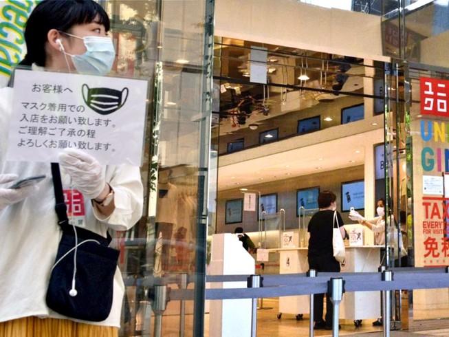 Khách hàng đeo khẩu trang mua sắm ở một cửa hàng Uniqlo ở thủ đô Tokyo, Nhật Bản hồi tháng 3-2020. Ảnh: REUTERS